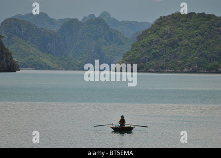 Mann-Ruderboot in Halong Bucht, Vietnam - Stockfoto