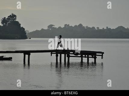 Junge zu Fuß entlang der Pier auf der Lagune in Sassandra, Elfenbeinküste, Westafrika - Stockfoto