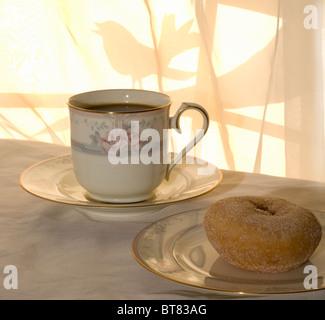 Ein sonniger Morgen mit Kaffee und Krapfen zum Frühstück, mit einem Vogel auf dem Baum vor dem Fenster.