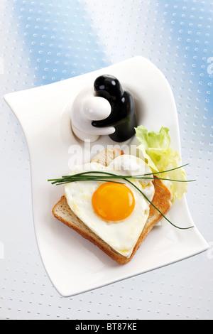Toast mit herzförmigen Spiegelei mit Schnittlauch und Figuren als Salz- und Pfefferstreuer - Stockfoto