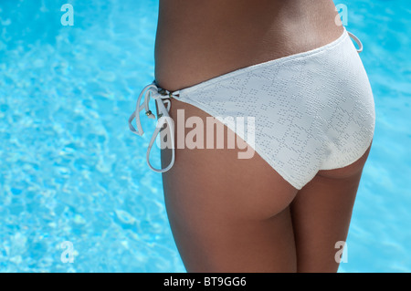 Eine Frau in einem weißen Bikini am Pool, Rückansicht