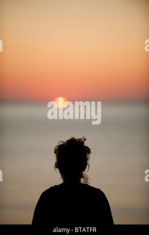 Rückansicht des Kopfes einer Frau Silhouette Blick auf Sonnenuntergang über Cardigan Bay, Aberystwyth Wales UK - Stockfoto
