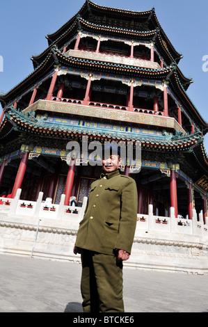 Ein chinesischer Mann kleidet sich in einen traditionellen grünen Mao-Anzug mit einer Baskenmütze außerhalb der - Stockfoto