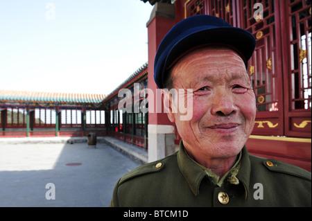 Ein chinesischer Mann lächelt und kleidet sich in einen traditionellen grünen Mao-Anzug mit einem Hut in der Sommer - Stockfoto