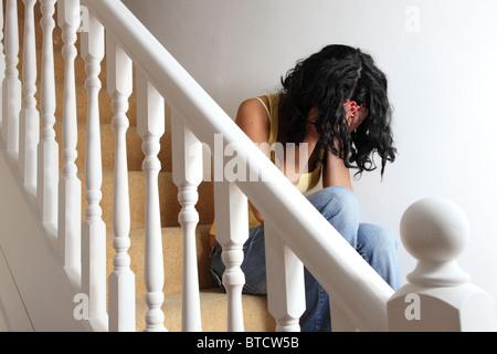 Frau sitzt auf der Treppe, die auf der Suche deprimiert. Modell und Besitz (Fotograf) veröffentlicht. - Stockfoto