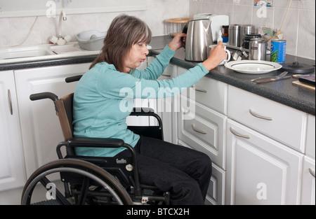 behinderte Frau Schmerzen sitzen im Rollstuhl, die Zubereitung von Speisen in der Küche - Stockfoto