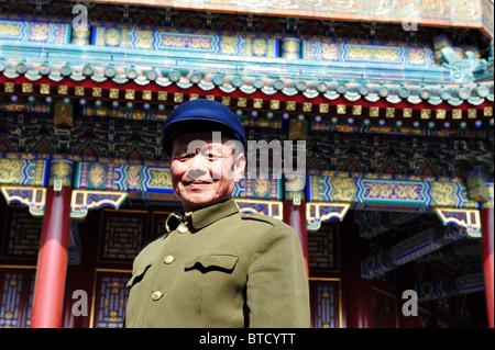 Ein chinesischer Mann lächelt gekleidet in traditionellen grünen Mao-Anzug mit einem Hut in der Sommer Palast Turm - Stockfoto