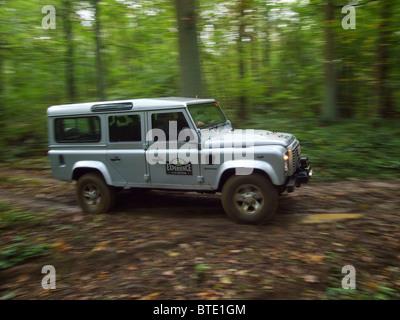 Silbernen Landrover Defender fahren durch einen Wald auf der Domaine d'Arthey Anwesen in Belgien - Stockfoto