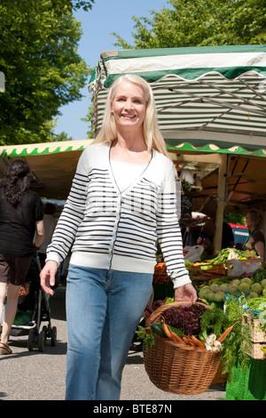 Frau, die ihre Einkäufe auf einem Wochenmarkt - Stockfoto