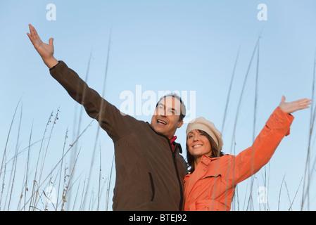 Älteres Paar im Freien, Arme angehoben, Porträt - Stockfoto