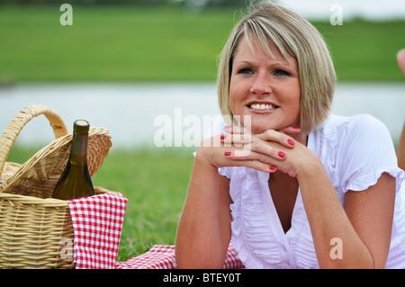 Junge, blonde Frau auf Picknick mit Wein, Korb, karierte Tuch und Serviette. - Stockfoto
