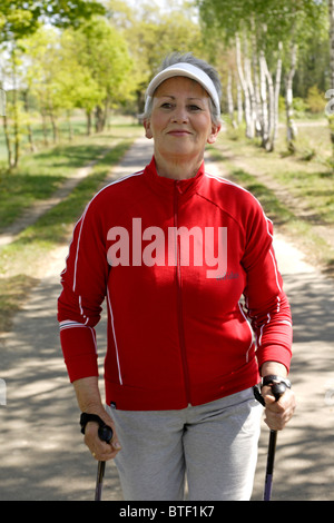 Ältere weibliche Person üben, nordic-walking - Stockfoto