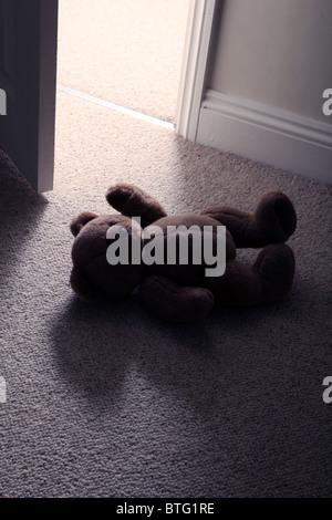 Des Kindes Teddybär liegend auf dem Boden ein Zimmer mit Teppichboden als eines Mannes Füße Schritt durch eine offene - Stockfoto