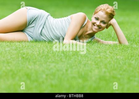 junge Frau entspannend auf Rasen - Stockfoto