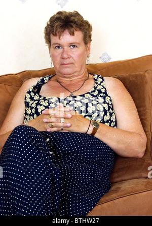 Applying sitzende natürliche Frau betrachten Kamera ernstem Gesicht unglücklich in die Kamera schauen - Stockfoto