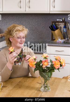 Frau, die Vermittlung von Blumen in einer Vase in der Küche - Stockfoto