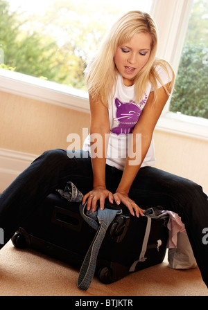 Mädchen kämpfen, um Koffer zu schließen - Stockfoto