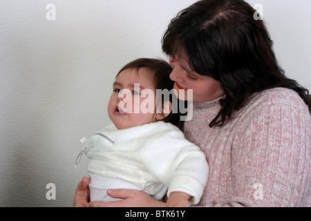 Mutter tröstet und halten ihr Plus size verärgert Babymädchen, das einen Wutanfall. - Stockfoto