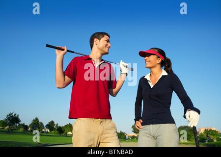 Golfplatz Nachwuchsspieler glücklich Paar posiert auf Bunker im Gespräch - Stockfoto