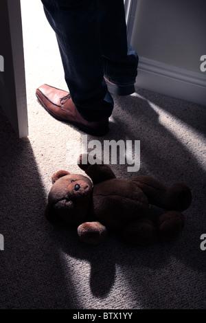 Beine und Carbonrigg treten hinter ein Kind Teddy Mannes tragen auf den Boden, um den Raum zu verlassen. - Stockfoto
