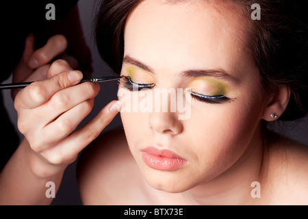 Make-up Artist Lidschatten auf ein junges weibliches Modell anzuwenden. - Stockfoto