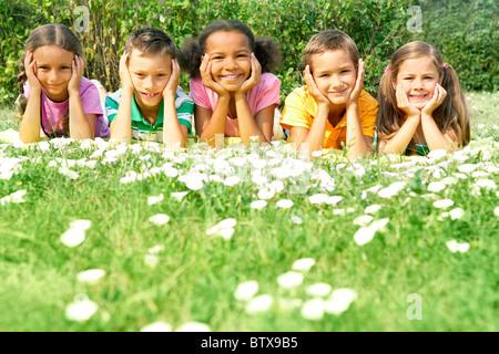 Porträt von niedlichen Kinder liegen auf dem grünen Rasen und Blick in die Kamera - Stockfoto