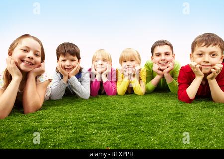 Bild von glücklichen jungen und Mädchen liegen auf einem grünen Rasen - Stockfoto