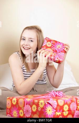 Ein junges Mädchen öffnet Geburtstagsgeschenke in ihr Schlafzimmer-UK - Stockfoto
