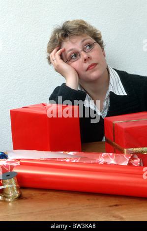 Weihnachtsgeschenke und Frau denken zu Hause am Tisch. - Stockfoto