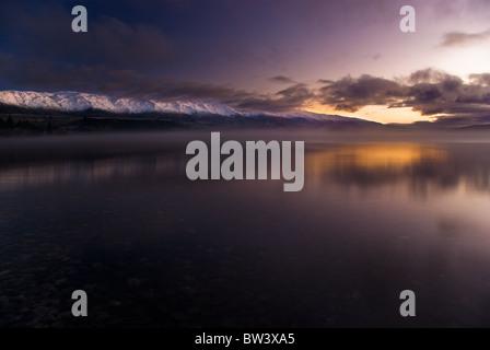 Sonnenaufgang über einem nebligen Lake Dunstan mit dem schneebedeckten Pisa im Hintergrund. Central Otago, Südinsel, Neuseeland.