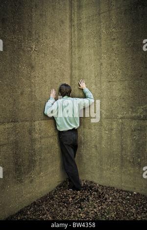 Mann stand an der Ecke von zwei Betonwände - Stockfoto