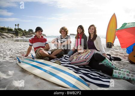 Freunde am Strand mit Surfbrett - Stockfoto