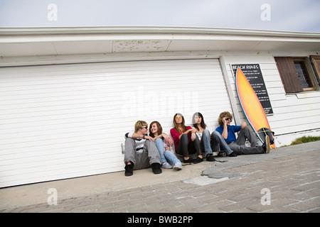 Freunde am Boden mit Surfbrett - Stockfoto