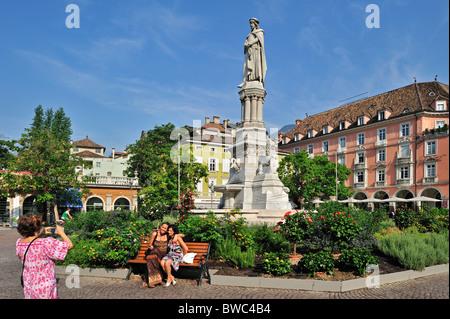 Touristen posieren vor der Statue von Walther von der Vogelweide am Waltherplatz in Bozen / Bozen, Dolomiten, Italien - Stockfoto