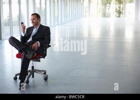 Geschäftsmann auf einem Stuhl im leeren Büro - Stockfoto