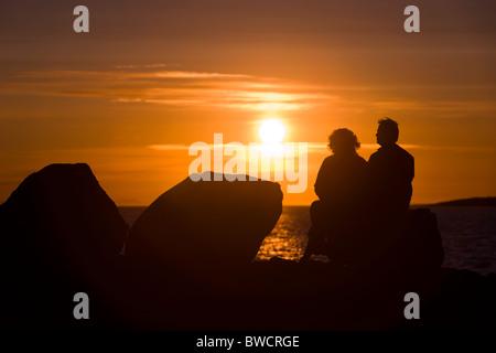 Menschen sitzen und genießen Sie die Mitternachtssonne-Einstellung über den Atlantischen Ozean. Reykjavik, Island. - Stockfoto