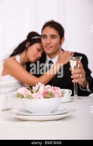 USA, Illinois, Metamora, Studioaufnahme von Braut und Bräutigam mit Blumen im Vordergrund - Stockfoto