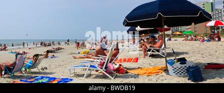Eine Panorama-Aufnahme des Menschen Sonnenbaden & spielen auf einem Teil des Sandstrandes in Myrtle Beach, SC auf - Stockfoto