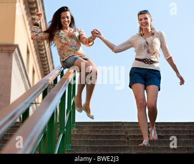 Junge Frauen, die Geländer Herunterrutschen - Stockfoto