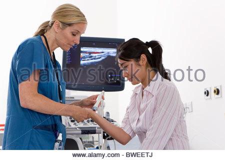 Techniker mit Ultraschall-Behandlung auf Patientís Handgelenk - Stockfoto