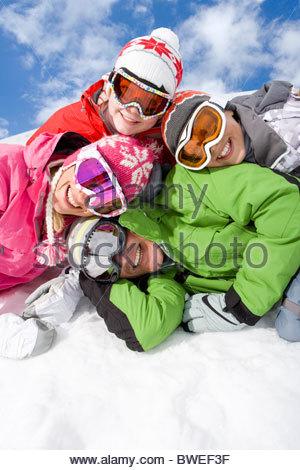 Familie im Schnee zusammen verlegen lächelnd - Stockfoto