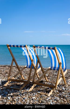 England, West Sussex, Bognor Regis, zwei blaue und weiße Liegestühle auf der Schindel Kiesstrand, der Blick auf - Stockfoto
