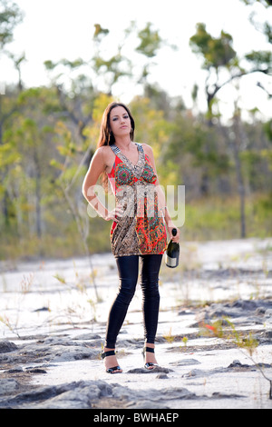 Attraktive junge Brünette Frau tragen helle Farbe Minikleid steht Holding Wein Flasche in das australische Outback - Stockfoto