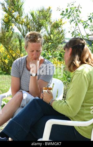Erwachsene Freundinnen reden auf der Rückseite Garten im Frühling, besorgt man eine fundierte Beratung - Stockfoto