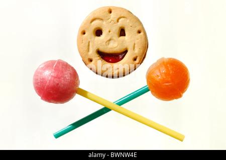 Lustig Lächeln Cookie und zwei Lutscher humorvolle Essenskonzept auf gelben Hintergrund isoliert - Stockfoto