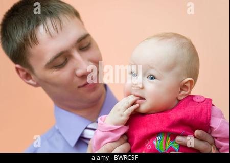 Europäische junger Mann schaut liebevoll seine kleine Tochter, die ihre Finger in den Mund nahm