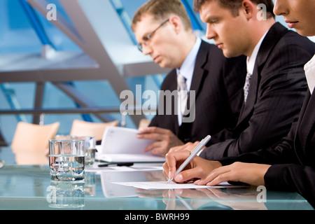 Reihe von ernsthaften Geschäftsleuten Notizen während der Konferenz - Stockfoto