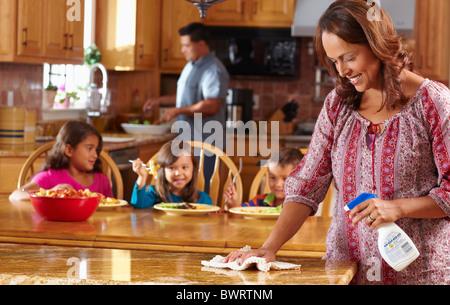 Mutter, Reinigung, während Kinder im Hintergrund Essen