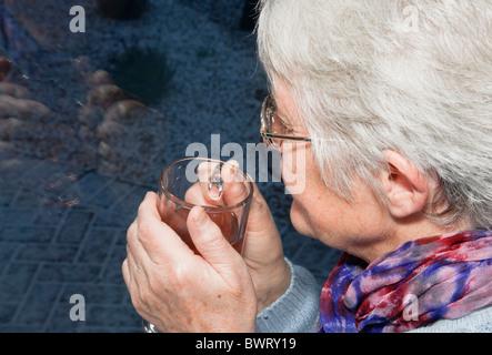 Nachdenklich, ältere Frau mit einem warmen Getränk mit Blick durch ein Fenster in einer kalten, dunklen Nacht mit - Stockfoto
