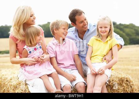 Familie sitzt auf Strohballen In abgeernteten Feld - Stockfoto